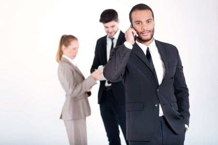 doings: Strict business call. Successful and smiling African businessman talking on cell phone while his colleagues are working on a tablet in the background on a gray background