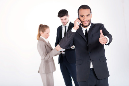 doings: Successful business call. Successful and smiling African businessman talking on a mobile phone showing a thumbs up while his colleagues are working on a tablet in the background Stock Photo