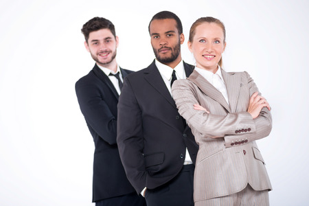 Top businessmen. Three successful and smiling businessmen standing in a row on a white background.