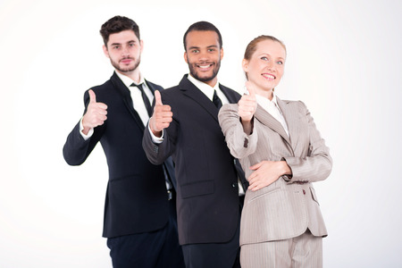 doings: Top businessmen. Three successful and smiling businessmen standing in a row on a white background showing a thumbs up. Stock Photo
