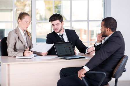 doings: Office affairs. Three successful business people sitting in the office and do business while businessmen communicate with each other and work at a laptop Stock Photo