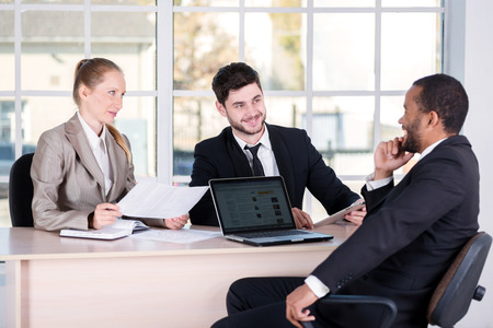 doings: Business meeting. Three successful business people sitting in the office and do business while businessmen communicate with each other and work at a laptop