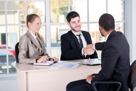 doings: Meeting of partners. Three successful business people sitting in the office and do business while businessmen shake hands with each other and work at a laptop Stock Photo
