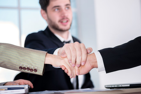 doings: Teamwork. Three successful business people sitting in the office and do business while businessmen shake hands with each other and work at a laptop