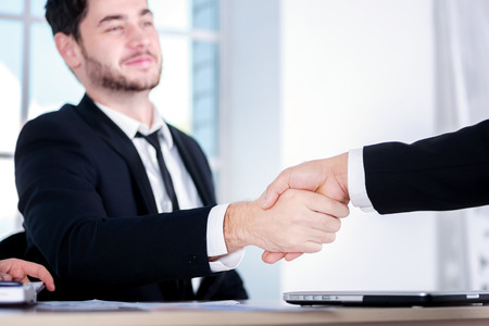 doings: Successful deal. Three successful business people sitting in the office and do business while businessmen shake hands with each other and work at a laptop