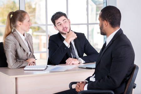 doings: Meeting with a client. Three successful business people sitting in the office and do business while businessman working at his desk