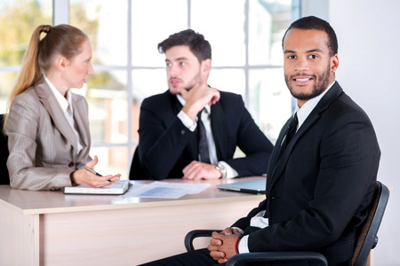 Portrait of African businessman. Three successful business people sitting in the office and do business while businessman working at his desk photo