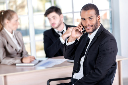 doings: African businessman talking on his mobile phone. Three successful business people sitting in the office and do business while businessman working at his desk Stock Photo