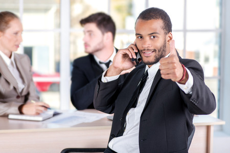 African businessman talking on his mobile phone and showing thumb up. Three successful business people sitting in the office and do business while businessman working at his desk photo