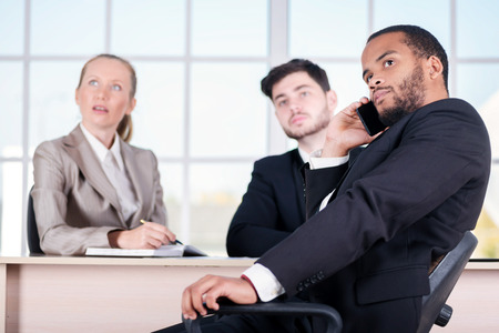 doings: African businessman talking on his cell phone. Three successful business people sitting in the office and do business while businessman working at his desk