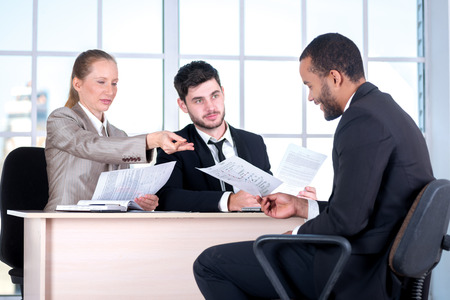 doings: Read the contract. Three successful business people sitting in the office and do business while businessman working at his desk