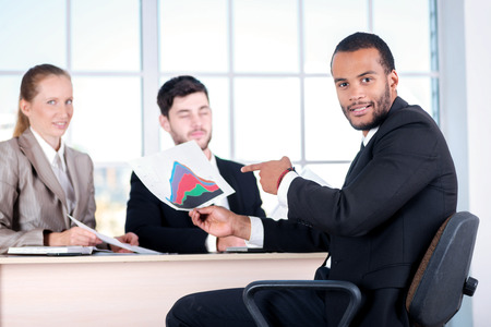 doings: Checking accounts. Three successful business people sitting in the office and do business while businessman considers documents