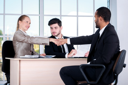 doings: Shaking hands. Three successful business people sitting in the office and do business while businessman considers documents Stock Photo