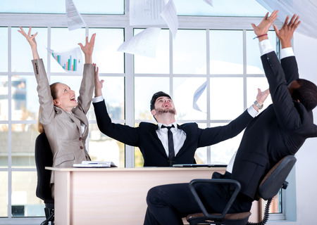 doings: Success in business. Three successful business people sitting in the office and throwing documents up while businessmen enjoyed their success.