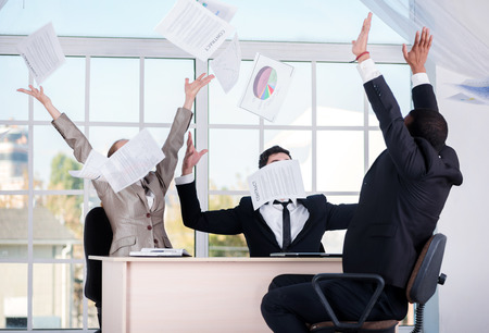 doings: Successful deal. Three successful businessmen throwing documents up while businessmen enjoyed their success sitting in the office. Stock Photo