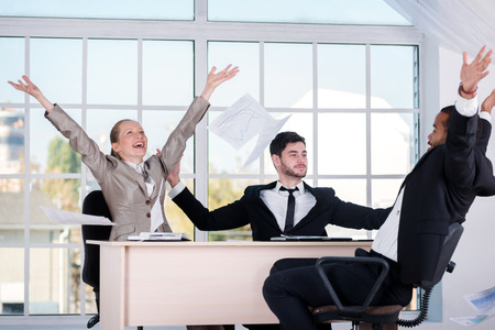 doings: Good day. Three successful businessmen throwing documents up while businessmen enjoyed their success sitting in the office. Stock Photo