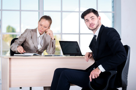 doings: Discussion of business problems. Two businessman sitting at the table until one man businessman looking at the camera.