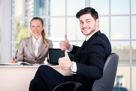 doings: Joyful businessmen. Two businessman sitting at the table until one man businessman looking at the camera and showing thumb up.