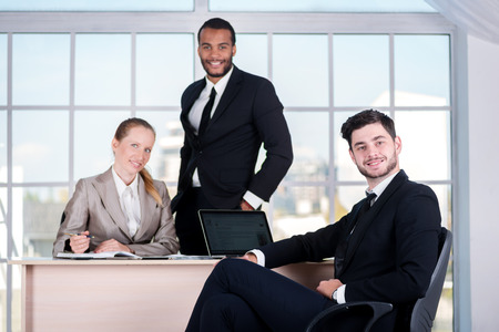 doings: Business team. Three businessman sitting at the table while three businessmen looking at the camera and smiling while standing in the office Stock Photo