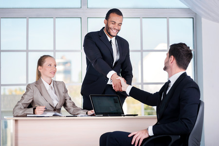 Business team. Three businessman sitting at the table while three businessmen looking at the camera and smiling while standing in office shaking hands with each other photo