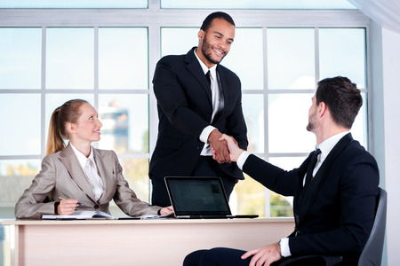 doings: Meeting business partners. Three businessman sitting at the table while three businessmen looking at the camera and smiling while standing in office shaking hands with each other Stock Photo