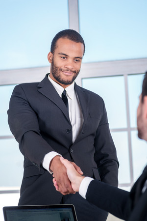 Meeting business partners. African businessman shaking hands with each other in the office photo