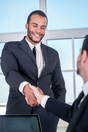 doings: Business dealings. African businessman shake hands with another businessman while businessmen standing in an office and smiling to each other