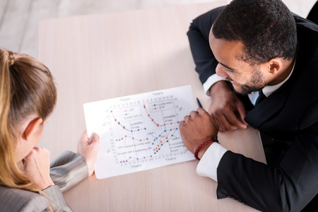 doings: The task. African businessman sees graphics on paper while another businessman sits at a table and holding a paper showing the data and graphs.