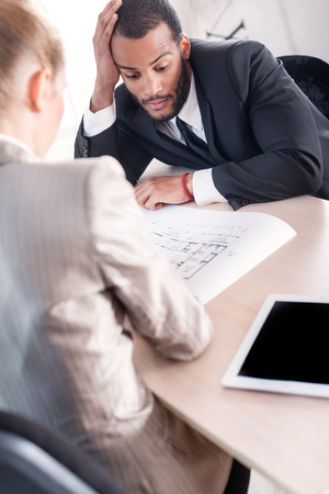 doings: Difficult task for the project. Successful African businessman considering a project while the second businessman sitting next to a table and holding a document in his hand