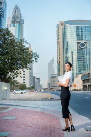 formal attire: Businessman in the city. Smiling businesswoman standing on a street in formal attire holding a laptop looks back at the camera. Arab businessman working on laptop in among the skyscrapers in Dubai. Stock Photo