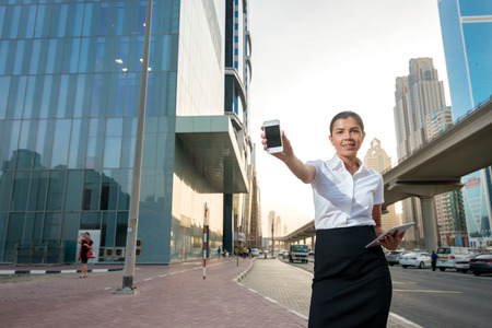 formal attire: Phone assistant businessman. Successful businesswoman standing in the street in formal attire. Businessman standing near skyscrapers in downtown and shows the phone directly into the camera