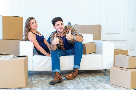 The joy of moving into the house. A loving couple holding box in hands and looking at the camera while a young and beautiful couple in love sitting on the couch in an empty apartment among boxes Stock Photo