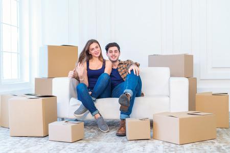 Nieuwe reparatie en verhuizing. Verliefde paar geniet van een nieuw appartement en houd de doos in zijn handen terwijl jong en mooi verliefde paar zittend op de bank in een leeg appartement tussen de vakken