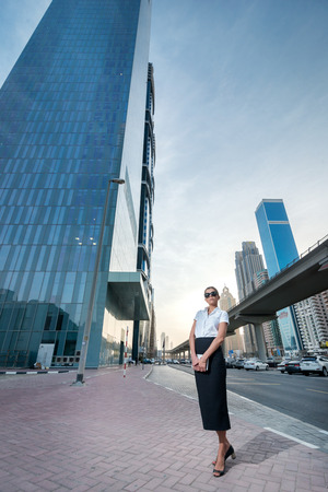 Great deals. Successful arabic businesswoman standing in the street in formal attire. Businessman standing near skyscrapers in Dubai downtown in sunglasses holding a tablet Stock Photo