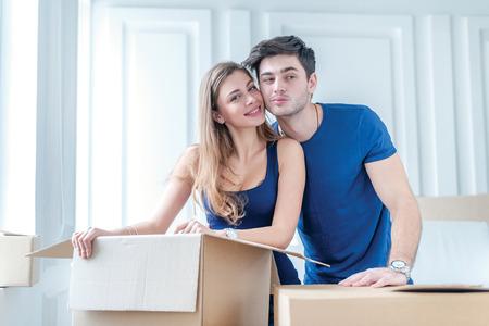 Bewegende, reparaties, nieuwe appartement. Een liefdevolle paar holding doos in handen en kijken naar de camera terwijl een jonge en mooie paar in liefde zittend op de bank in een leeg appartement onder dozen