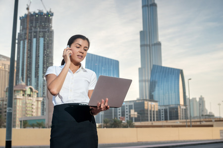 attire: Business. Confident businesswoman standing on a street in formal attire holding a laptop while talking on cell phone. Arab businessman working on laptop in among the skyscrapers in Dubai