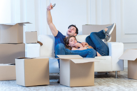 Moving to a new life. A girl and a guy holding boxes for moving the hands and smiling at the camera while a couple in love standing at the window among boxes Standard-Bild