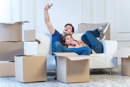 Verhuizen naar een nieuw leven. Een meisje en een man met dozen voor het verplaatsen van de handen en lacht naar de camera terwijl een paar in liefde staande bij het raam onder dozen