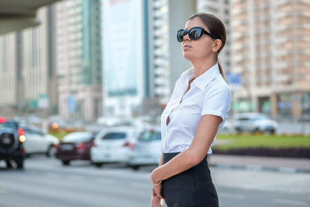 formal attire: Confident woman. Successful arabic businesswoman standing in the street in formal attire. Businessman standing near skyscrapers in Dubai downtown in sunglasses holding a tablet Stock Photo