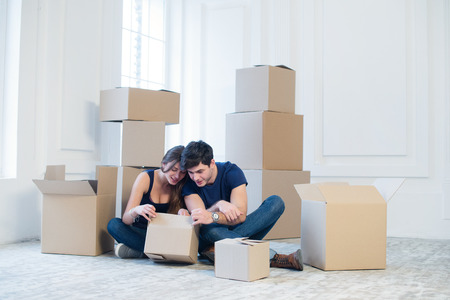 The joy of moving into the house. A loving couple holding box in hands and looking in the box while a young and beautiful couple in love sitting on the couch in an empty apartment among boxes