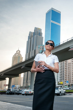 formal attire: Arab trade. Successful arabic businesswoman standing in the street in formal attire. Businessman standing near skyscrapers in Dubai downtown in sunglasses holding a tablet
