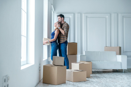 love life: Moving, repairs, new life. Couple in love enjoys a new apartment and keep the box in his hands while young and beautiful couple in love sitting on the couch in an empty apartment among boxes