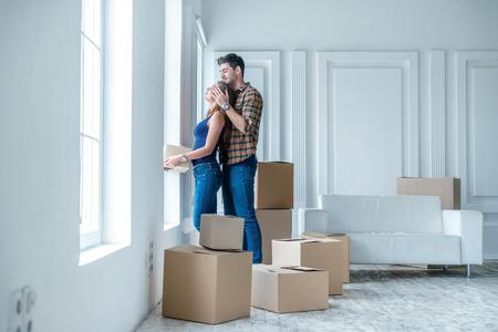 Verhuizen, reparaties, nieuw leven. Verliefde paar geniet van een nieuw appartement en houd de doos in zijn handen terwijl jonge en mooie verliefde paar zittend op de bank in een lege appartement tussen de vakken