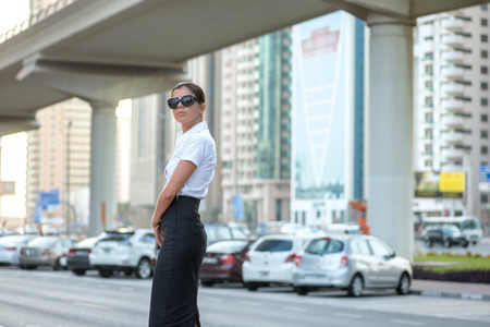 formal attire: Strict business. Confident arabic businesswoman standing in the street in formal attire. Businessman standing near skyscrapers in Dubai downtown in sunglasses waiting for a taxi