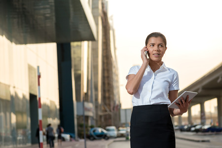 attire: Call the customer. Successful businesswoman standing in the street in formal attire. Businessman standing near skyscrapers in Dubai downtown at talking on cell phone