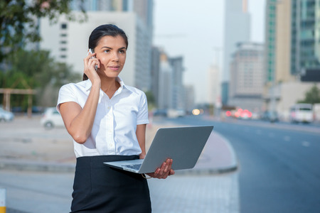 formal attire: New challenges. Confident businesswoman standing on a street in formal attire holding a laptop while talking on cell phone. Arab businessman working on laptop in among the skyscrapers in Dubai