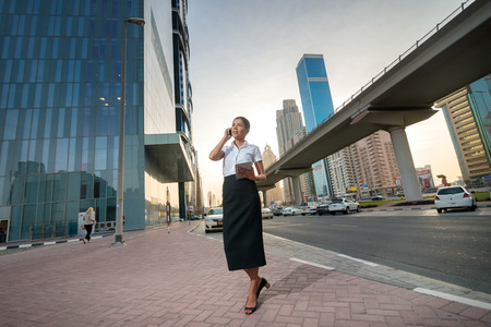 business attire: Call the customer. Successful businesswoman standing in the street in formal attire. Businessman standing near skyscrapers in Dubai downtown at talking on cell phone