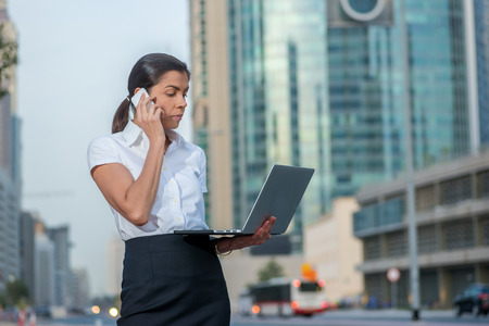 formal attire: Solving problems. Successful businesswoman standing in the street in formal attire holding a laptop while talking on cell phone. Arab businessman working on laptop in among the skyscrapers in Dubai