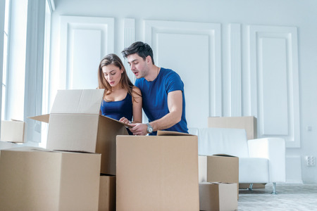 home keys: Moving to a new life. A girl and a guy holding boxes for moving the hands and smiling at the camera while a couple in love standing at the window among boxes Stock Photo