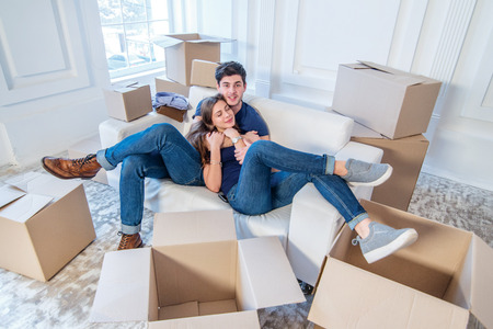 people moving: The joy of moving into the house. A loving couple holding box in hands and looking at the camera while a young and beautiful couple in love sitting on the couch in an empty apartment among boxes Stock Photo